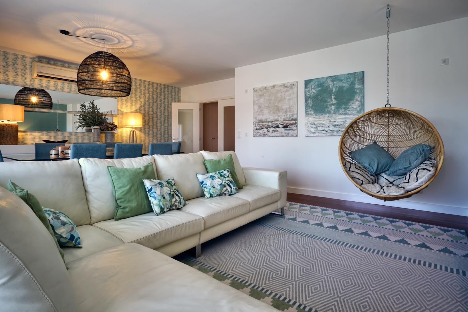 Sala de estar em tons verdes e com baloiço